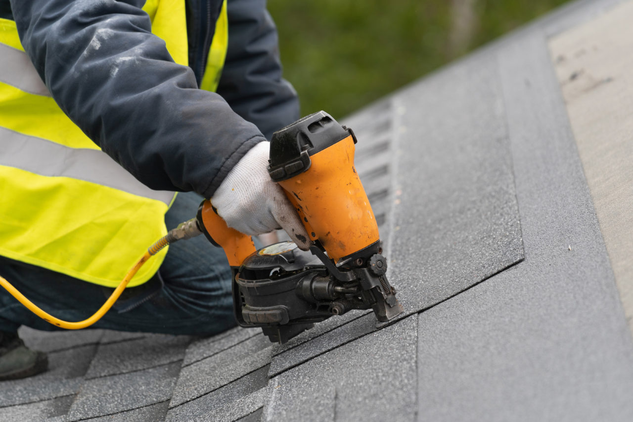 A roofer installing a shingle roof on a home in Steinbach